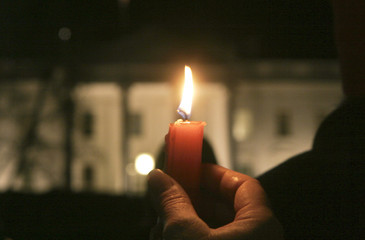 A protester holds a candle with the White House in the background during an anti-war rally and candlelight vigil in Washington