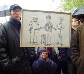 A SERB BOY HOLDS BANNER WITH CARTOON DURING PROTEST IN GRACANICA.