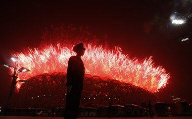 A paramilitary policeman keeps watch as fireworks illuminate the sky over the National Stadium during the opening ceremony of the Beijing 2008 Olympic Games