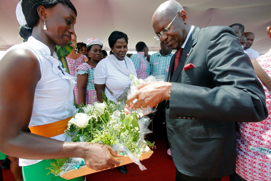 Pascal Abinan Kouakou, Ivory Coast Minister of Public Service, distributes lily of the valley flowers to women workers during May Day celebrations in Abidjan
