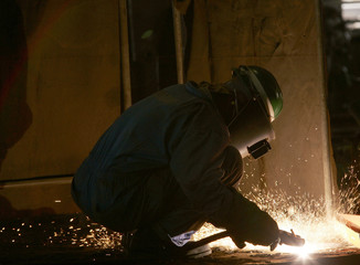 A worker welds steel plates at the Dubai Dry Docks workshop