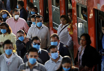 People wear surgical face masks as they get off from the Metro in Mexico City
