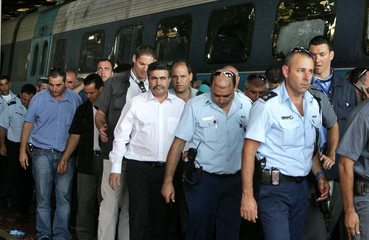Israeli Defense Minister Amir Peretz visits the scene of a rocket attack in Haifa