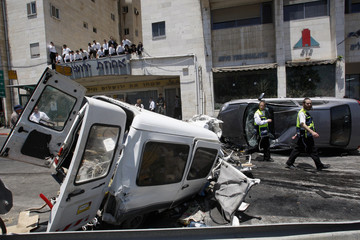 Israeli rescue workers walk past damaged vehicles at scene of attack in Jerusalem