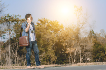 Man on smart phone and shoulder bag brown leather.