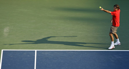 Roger Federer of Switzerland serves to Gilles Muller of Luxembourg during their quarter-final match at the U.S. Open tennis tournament in Flushing Meadows in New York.