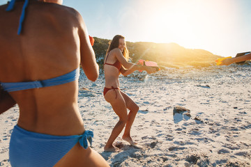 Female friends playing with water guns on the beach