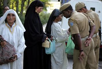 Indian paramilitary soldier checks the belongings of Kashmiri Muslim women during a gun battle at Harwan, Srinagar