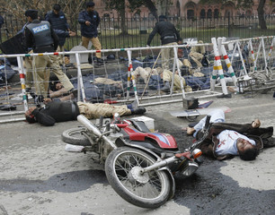 Police help their colleagues injured in a suicide bombing outside a court in the centre of the Pakistani city of Lahore