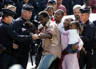 French riot policemen tussle with a family on Fraternite street in Paris September 2, 2005. Police h..