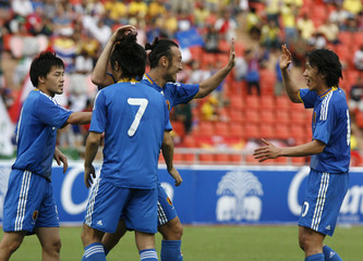 Japan's Tanaka celebrates with teammate Nakamura after scoring goal against Thailand in Bangkok