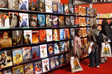 Young visitors browse hard cover cartoon books at the annual Paris book fair