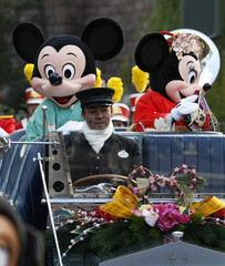 Disney cartoon characters Mickey (L) and Minnie Mouse, dressed in kimonos, wave from an open car during a New Years parade at Tokyo Disneyland in Urayasu