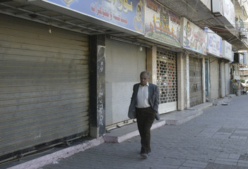 A man walks past closed shops during curfew in Baghdad