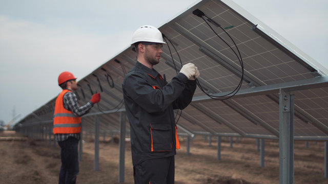 The builders connecting the solar energy panels with the wires.