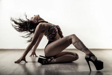 Young beautiful slim girl dancer on high heels posing go-go on the floor