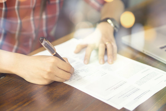 Businessperson Signing Contract,Man writing paper at the desk with pen and reading books at table with basic business Form document working in office ,morning light ,selective focus.