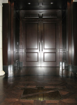 A set of mahogany double-doors flanked by Stanford's corporate eagle logo leads to the cavernous personal office of Texas billionaire Allen Stanford in Houston