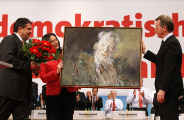 New SPD leader Gabriel new General Secretary Nahles present flowers and painting to former party leader Muentefering at party congress in Dresden