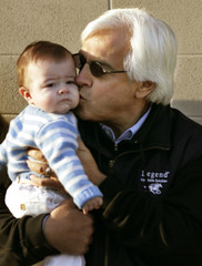 Trainer Bob Baffert gives his 4-month old baby Bode Baffart a kiss out side his barn at Churchill Downs.