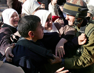 Palestinian students scuffle with an Israeli soldier in Hebron