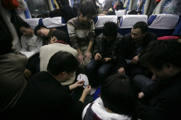 Passengers play cards on overcrowded overnight train from Beijing to Chengdu