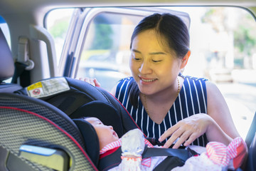 Smiling Asian women,Mother takes care about her daughter in a cars,helps her child  fasten  little young baby in car seat,safety belt for infant,parent is keeping child safe when riding in a vehicle.