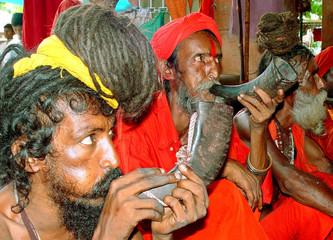 INDIAN HINDU SADHUS OR HOLY MEN BLOW PEPA A TRADITIONAL INSTRUMENT IN GUWAHATI.