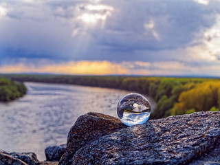 Magic glass ball on old stones. In the background is the bend of the river, spring forest and cloudy sky