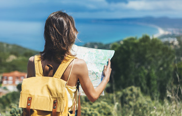 Hipster tourist hold and look map on trip, lifestyle concept adventure, traveler with backpack on background mountain and blue sea landscape horizon, young girl hiker pointing hands on trekking plan