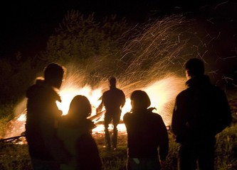 People observe a fire as they gather during a rally to mark Labour Day in Zagorica