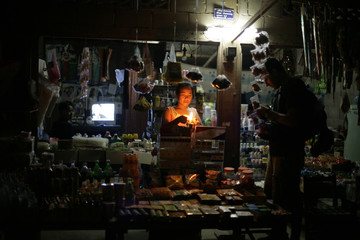 A tourist buys from a shopkeeper in Pak Beng