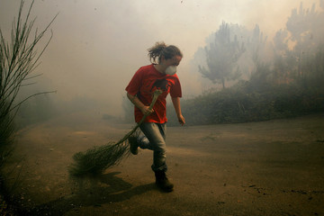 A villager runs during a forest fire in Pontecaldelas