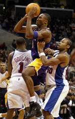 LAKERS KOBE BRYANT PASSES BALL OFF PAST CLIPPERS DOOLING AND MAGGETTEIN LOS ANGELES.