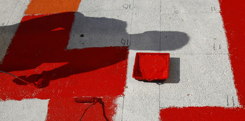 A pupil casts his shadow on the pavement as he copies a Kandinsky painting on the Weilheim market place