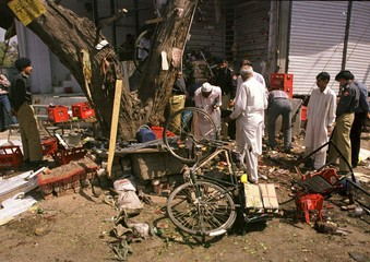 PAKISTANI POLICE OFFICIALS SEARCHING THE DEBRIS.