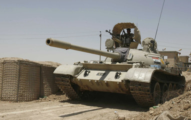 An Iraqi tank takes up position at an army checkpoint in Amara