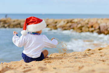 Back view of cute little Santa Claus on sandy beach. Sunny exotic blue sky background outside