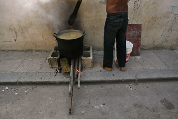 """A man cooks """"Caldosa,"""" a typical Cuban stew, on a street in Old Havana"""
