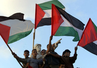 Palestinian youths hold flags next to a statue of an unknown Palestinian soldier during a demonstrat..