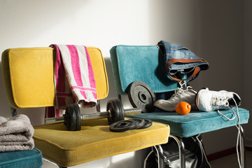Detail of a teenager's room with dumbells, towel and shoes. Interior sports and gym concept.