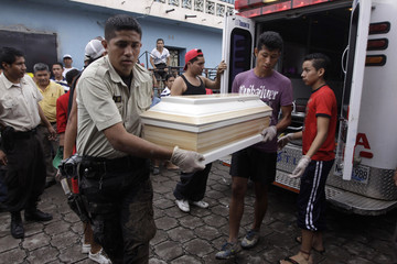 Rescue workers carry a coffin with the body of a person who died due to flooding in San Martin near San Salvador