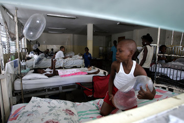 A Haitian boy plays with a condom-shaped balloon in the paediatrics ward of the General Hospital in Port-au-Prince during World AIDS Day