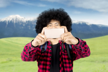 Afro man using a smartphone for take pictures