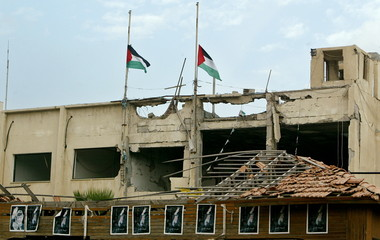 Palestinian flags fly half-staff over the damaged headquarters of President Yasser Arafat in Gaza, N..