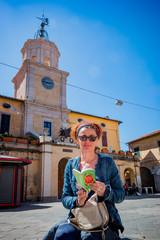 Femme sur un banc devant l'église de Orbetello en Toscane