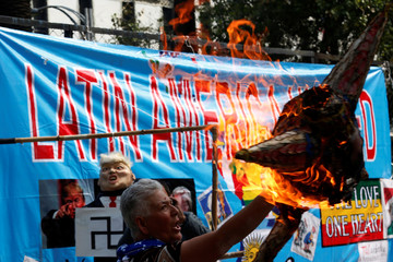 An activist burns a pinata with a picture of U.S. President Donald Trump during a demonstration on International Labor Day in Mexico City