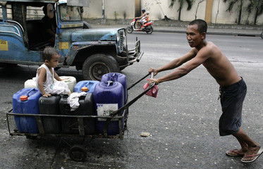 A man pushes a cart with plastic containers filled with water along a busy street in Manila