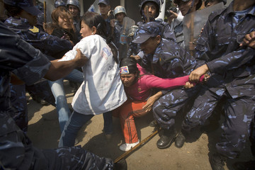 Police struggle to detain a pro-Tibet activists protesting outside UN building in Kathmandu