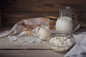 Fresh dairy products (milk, cottage cheese, sour cream) and wheat on rustic wooden background.